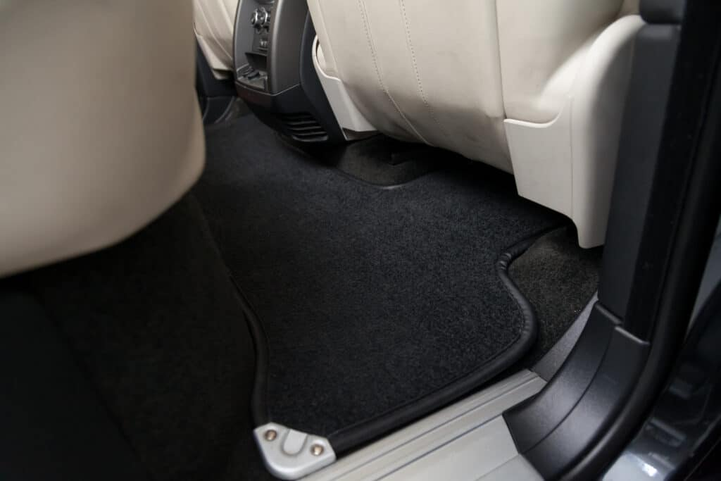 Clean car floor mats of black carpet under rear passenger seat in the workshop for the detailing vehicle before dry cleaning. Auto service industry. Interior of sedan.